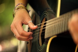 Girl playing fingerstyle guitar